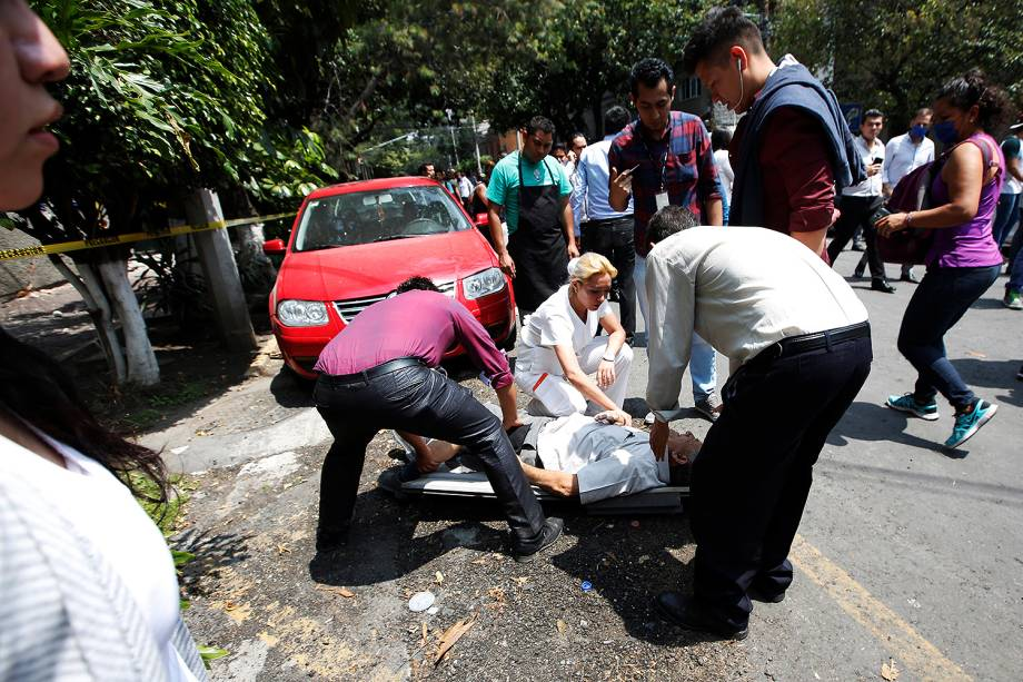Equipes de resgate e voluntários removem destroços de um prédio que desabou, à procura de sobreviventes, na Cidade do México