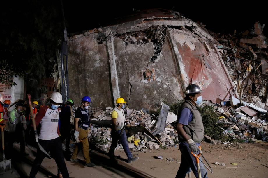 Trabalhadores passam em frente a um prédio abalado pelo terremoto de 7,1 graus de magnitude que atingiu o México - 20/09/2017