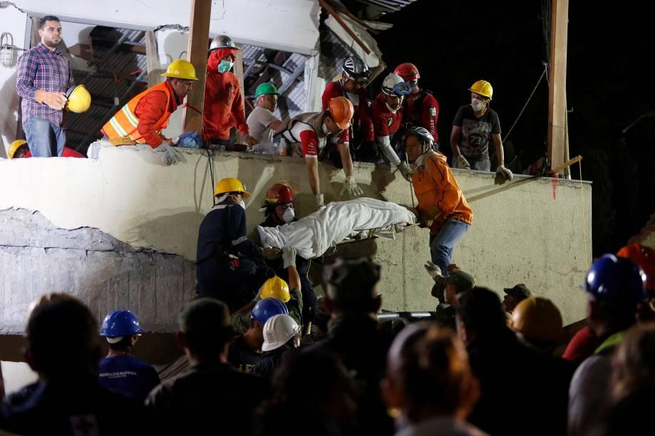 Membros da equipe de resgate removem um corpo após vasculhar os escombros da escola Enrique Rebsamen, na Cidade do México, em busca de sobreviventes do terremoto - 20/09/2017