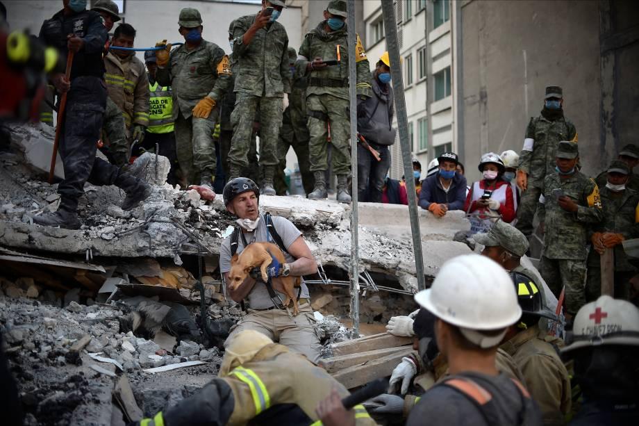 Um homem retira um cachorro dos escombros de um prédio destruído após a passagem de um terremoto na Cidade do México, no aniversário de 32 anos de outro terremoto devastador que ocorreu em 1985 - 20/09/2017