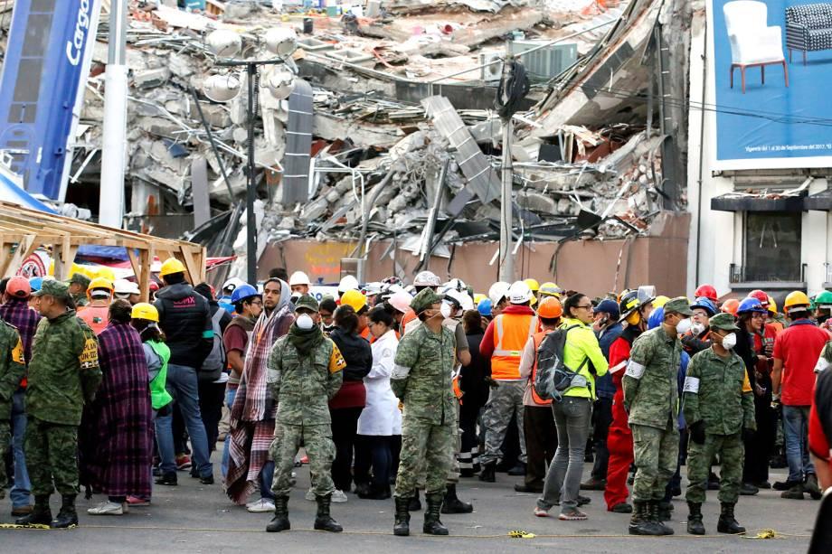 Soldados e equipes de resgate aguardam em uma rua após sentirem um novo terremoto na Cidade do México. Ao fundo, destroços do terremoto que atingiu o méxico na terça-feira (19) - 23/09/2017