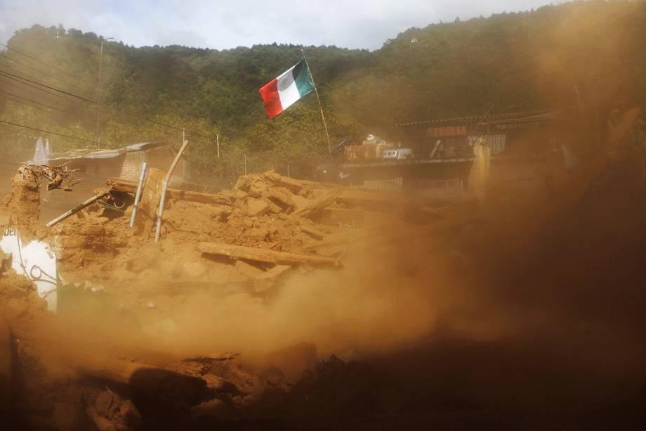 Bandeira do México é erguida em meio a escombros, em Tecomatlan - 23/09/2017