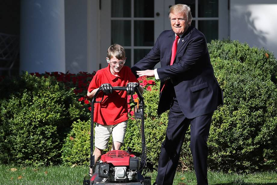 O menino Frank Giaccio, de 11 anos, corta a grama na Casa Branca, ao lado do presidente Donald Trump, Washington - 15/09/2017