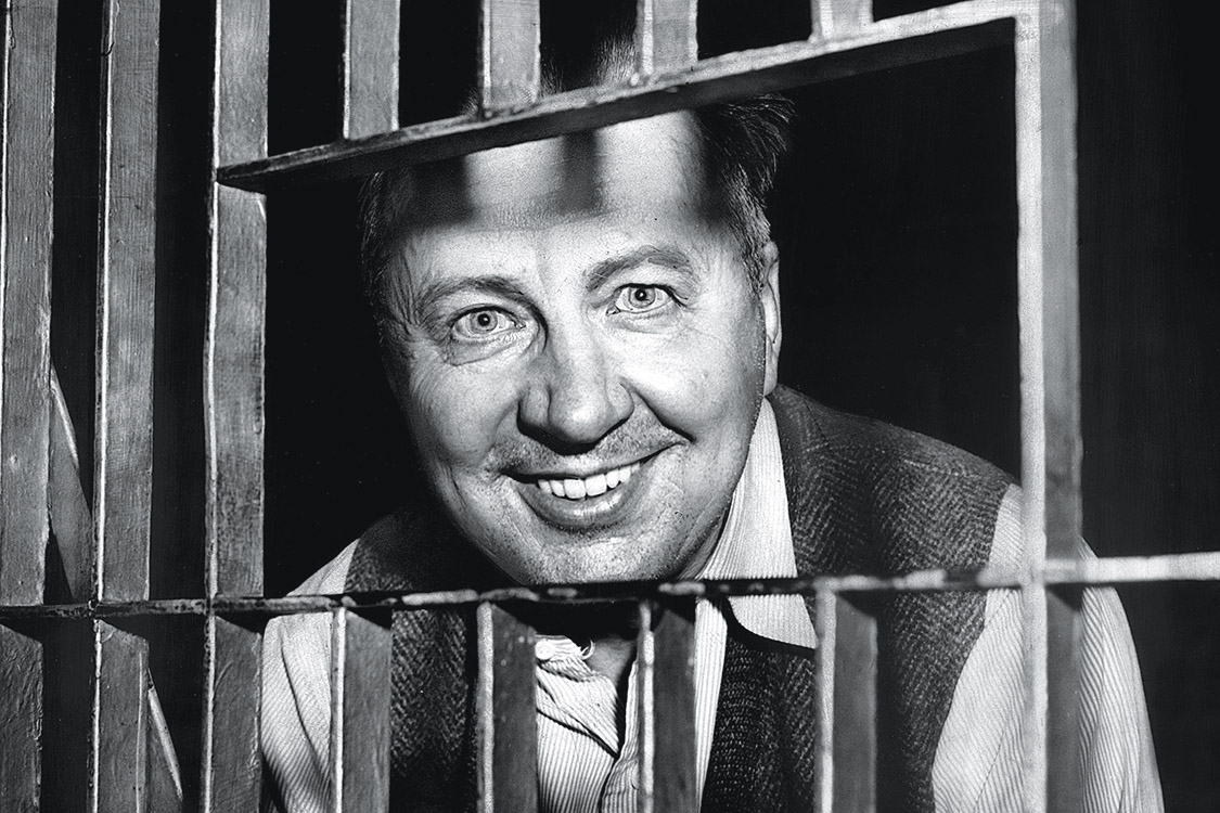 """97308464 - UNITED STATES - JANUARY 22: George Metesky, 53 years old, who confessed to being the """"Mad Bomber"""", looks through the bars of his cell at the Waterbury, Conn. Police Station. Metesky roamed the city planting bombs for 16 years before his arrest, and later was sent to a mental institution. Credito: Judd Mehlman/NY Daily News Archive/Getty Images"""
