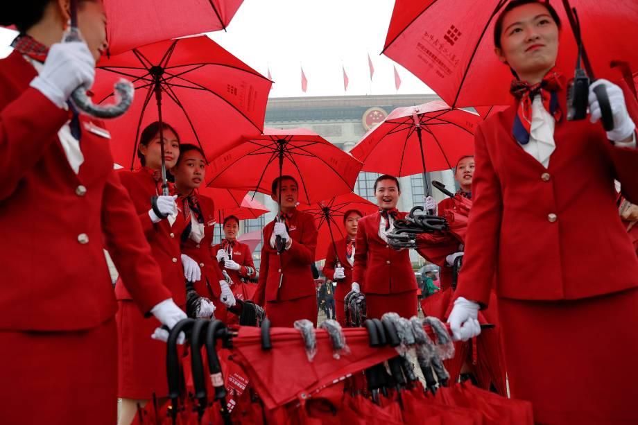 Mulheres se encarregam de cuidar dos guarda-chuvas usados pelos delegados que chegam para a sessão de abertura do 19º Congresso Nacional do Partido Comunista da China, no Grande Salão do Povo em Pequim, na China - 18/10/2017