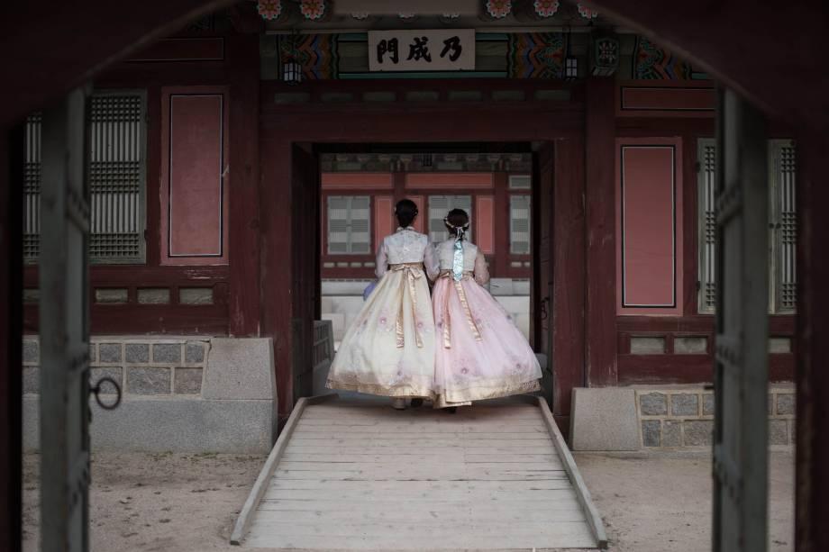 Duas mulheres usam o vestido tradicional hanbeok coreano na entrada do palácio Gyeongbokgung, em Seul, durante o feriado Chuseok, de uma semana no qual as famílias geralmente oferecem agradecimentos e orações a seus antepassados - 03/10/2017