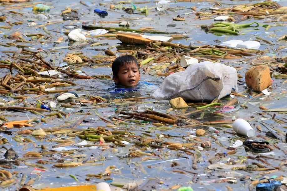 Menino coleta garrafas de plástico recicláveis em meio ao lixo ao longo da costa da Baía de Manila, na área das favelas de Baseco Filipinas - 16/10/2017