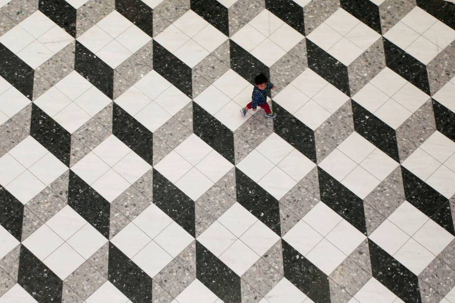 Um garoto é fotografado andando sobre um piso de construção geométrica dentro de um shopping center, em Tóquio, no Japão - 18/10/2017