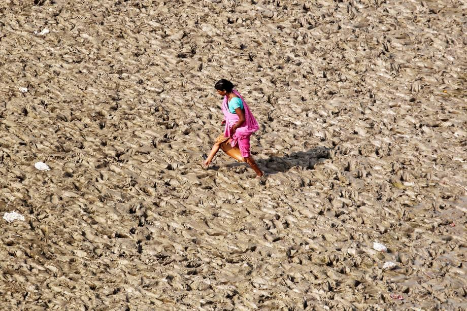 Uma mulher é vista caminhando sobre uma parte lamacenta do Rio Ganges, na cidade de Allahabad, na Índia - 19/10/2017