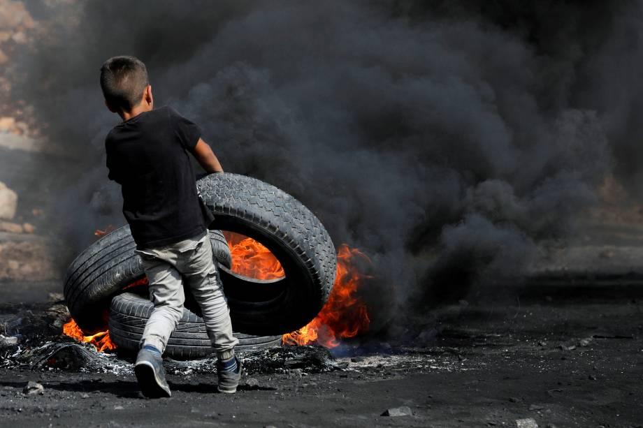 Um menino palestino coloca um pneu em chamas durante um confronto com tropas israelenses perto do assentamento judaico de Qadomem, na aldeia de Kofr Qadom, perto de Nablus, no território da Palestina - 20/10/207