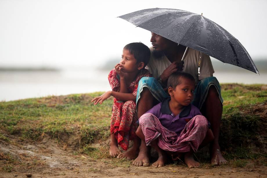 Refugiados se protegem da chuva enquanto aguardam permissão do Exército para prosseguirem viagem, em Teknaf, região de Bangladesh - 31/10/2017