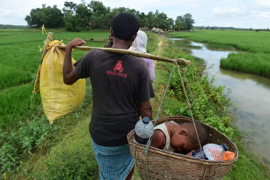 Um refugiado rohingya carrega uma criança dentro de um cesto enquanto caminha na área de uma terra de ninguém, entre Bangladesh e Myanmar, na região de Palongkhali, ao lado da Ukáia - 19/10/2017