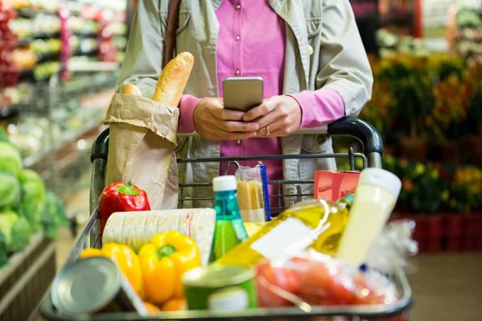 Mulher mexendo no celular enquanto faz compras