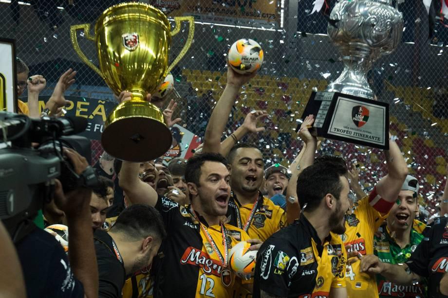 Falcão e Rodrigo erguem troféus durante a comemoração do bicampeonato da Liga Paulista de Futsal, na Arena Sorocaba, em São Paulo