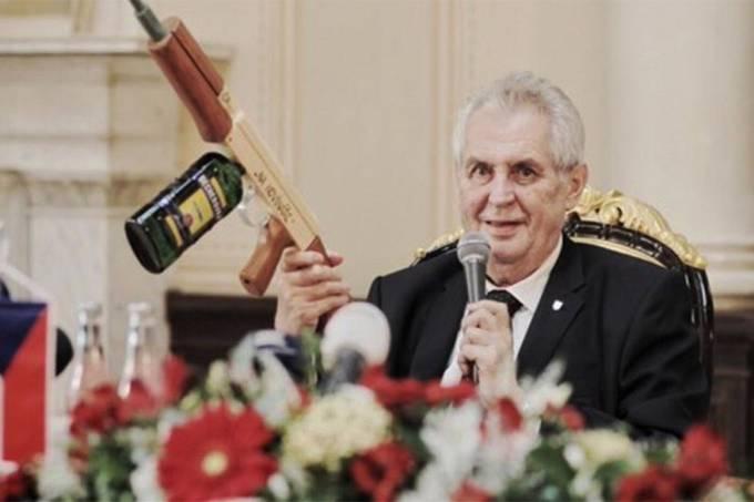 O presidente checo Milos Zeman segura uma arma falsa em coletiva de imprensa