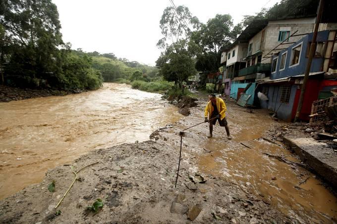 Morador retira lama após enchente do rio Tribi devido à Tempestade Tropical Nate, na Costa Rica – 05/10/2017
