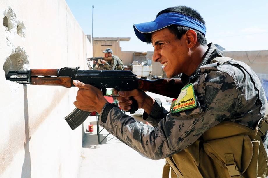Soldados das Forças Democráticas Sírias atiram contra militantes do Estado Islâmico, por buracos em parede no topo de uma casa em Raqqa - 01/10/2017