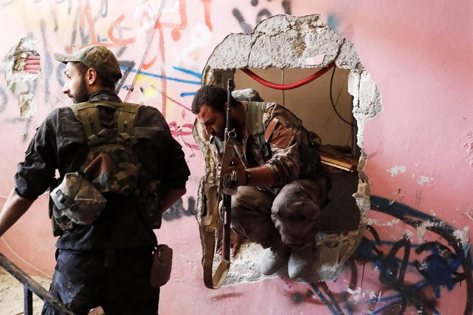 Soldados das Forças Democráticas Sírias passam por um buraco na parede enquanto se posicionam para combater militantes do Estado Islâmico, em Raqqa - 04/10/2017