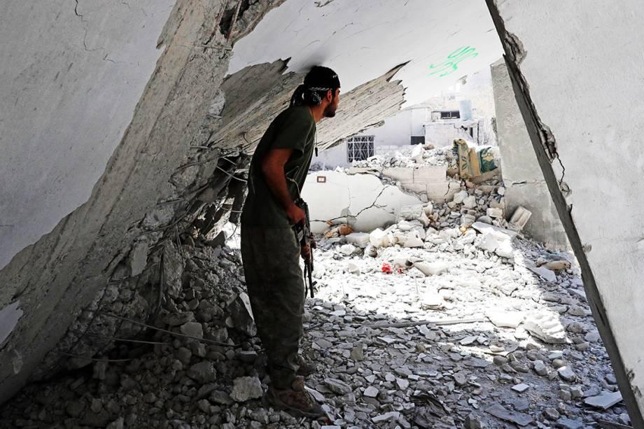Soldado das Forças Democráticas Sírias se protege em meio a escombros durante combate contra militantes do Estado Islâmico, em Raqqa - 04/10/2017