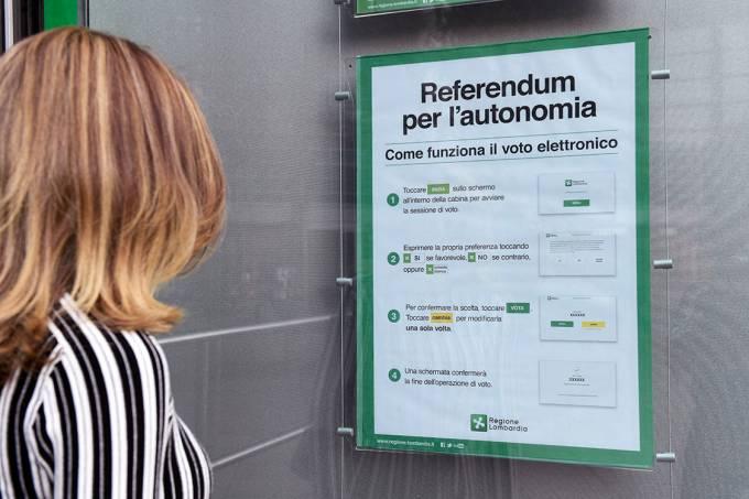 Mulher observa cartaz sobre referendo na região de Lombardia, em Milão