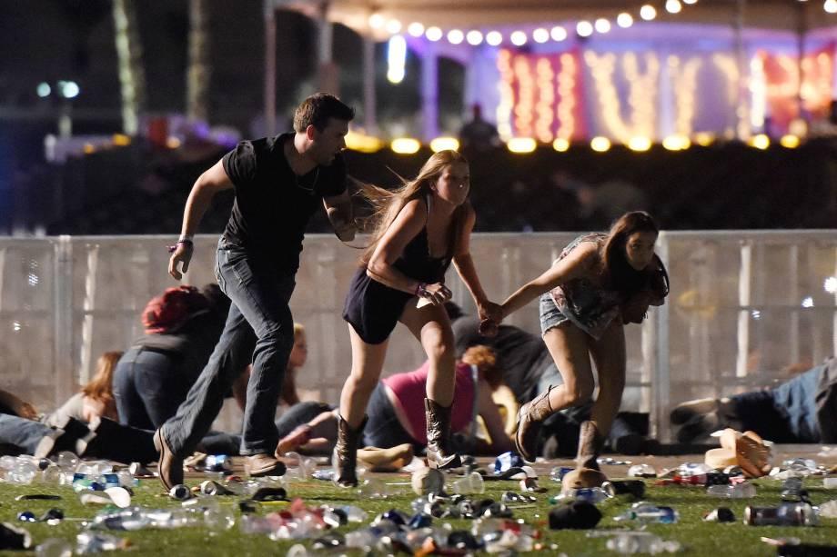 Pessoas correm ao ouvir tiros durante o festival 'Route 91 Harvest', em Las Vegas, no estado americano de Nevada. O atirador disparava do 32º andar de um prédio em frente ao espaço dos shows - 02/10/2017