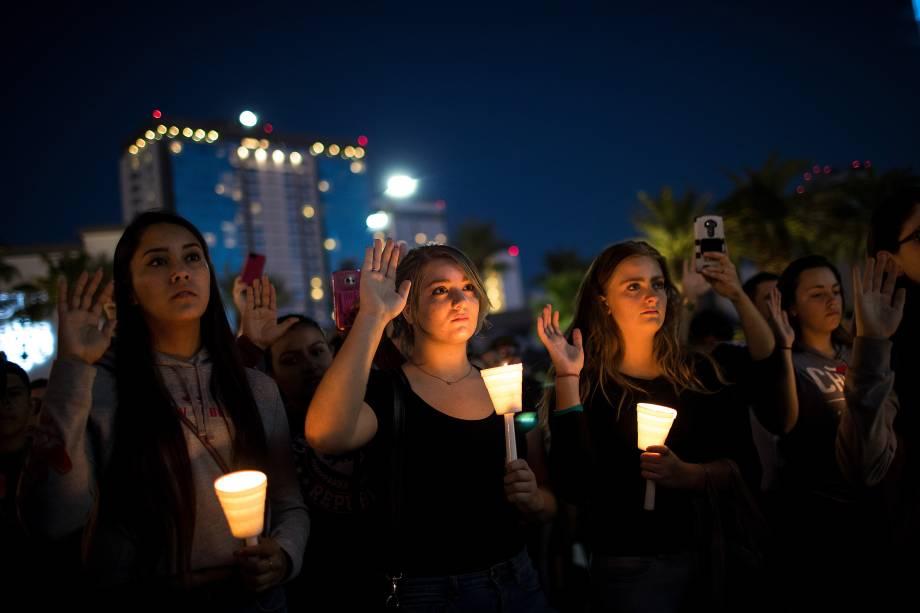 Pessoas se encontram no cruzamento da Avenida Sahara com a Las Vegas Boulevard, e levantam a mão direita clamando por um mundo mais pacífico durante homenagem às vitimas do tiroteio no festival de música country 'Route 91 Harvest' em Las Vegas - 02/10/2017