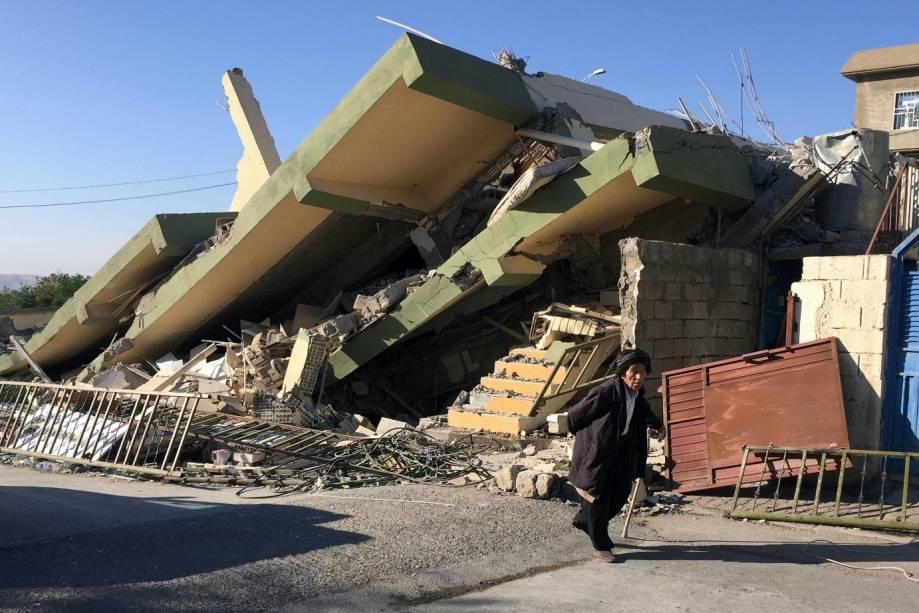 Homem atravessa um edifício danificado após um terremoto em Darbandikhan, na região de Sulaimaniya, no Iraque - 13/11/2017