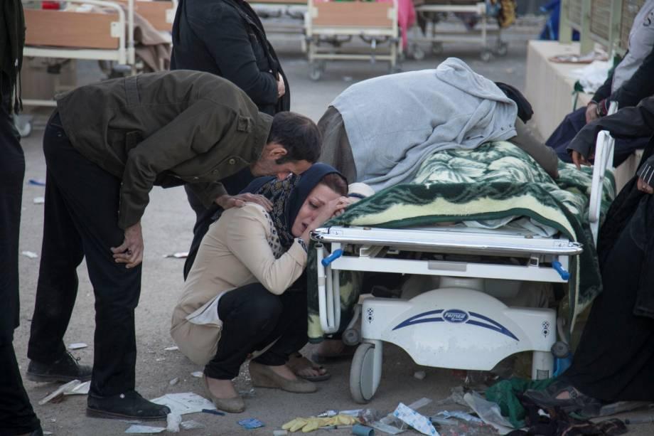 Mulher chora ao lado do corpo de uma vítima após um terremoto no condado de Sarpol-e Zahab, em Kermanshah, no Irã - 13/11/2017