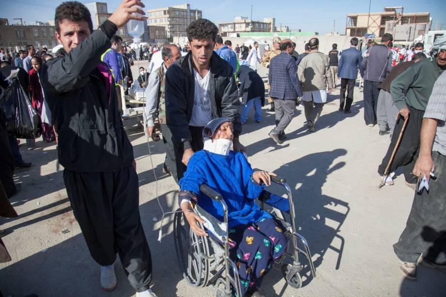 Homens auxiliam uma mulher ferida após um terremoto no condado de Sarpol-e Zahab, em Kermanshah, no Irã - 13/11/2017