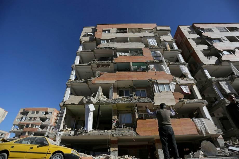 Homem reage ao olhar para um edifício danificado após um terremoto no condado de Sarpol-e Zahab, em Kermanshah, no Irã - 13/11/2017