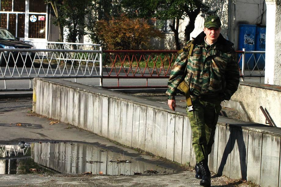 Militar caminha por rua nos arredores de Sukhumi.