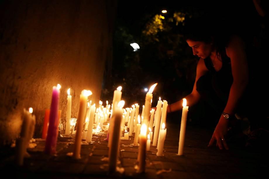 Mulher acende velas em frente ao Instituto Politécnico de Rosário, na Argentina, em memórias às vítimas do ataque em Nova York - 01/11/2017