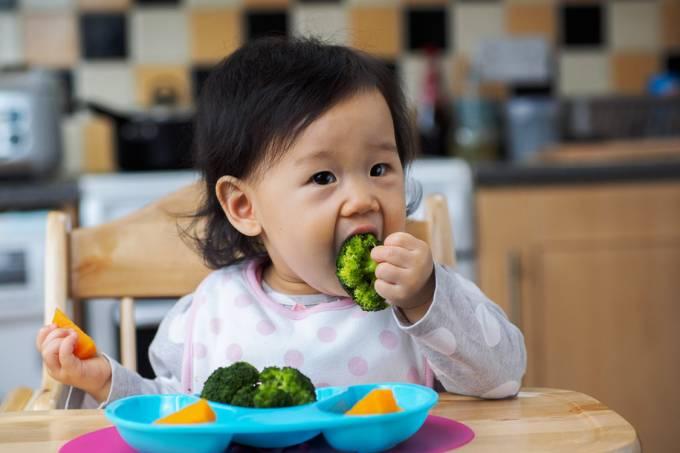 Criança comendo com as mãos