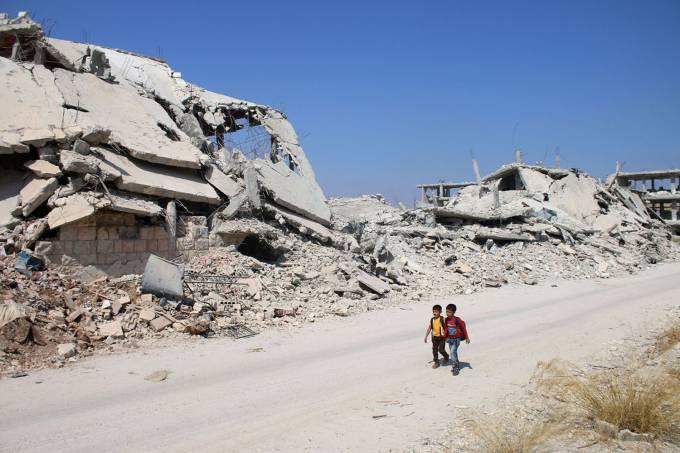Crianças caminham próximas a edifícios destruídos em área controlada por rebeldes, na cidade de Daraa, Síria – 17/09/2017