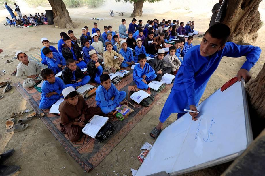 Crianças afegãs são fotografadas estudando em uma área aberta no distrito de Ghani Khel, na cidade de Jalalabad, no Afeganistão - 06/11/2017