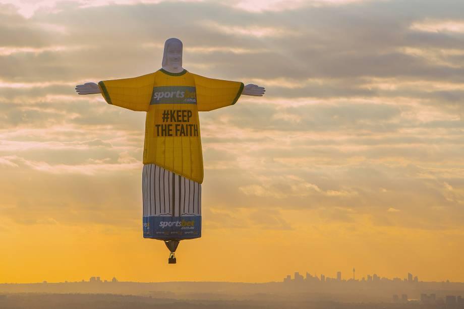 Uma representação do Cristo Redentor inflável é vista durante o pôr do sol no céu da cidade de Sidney, na Austrália. O boneco é parte de uma campanha publicitária em uma empresa de apostas online - 13/11/2017