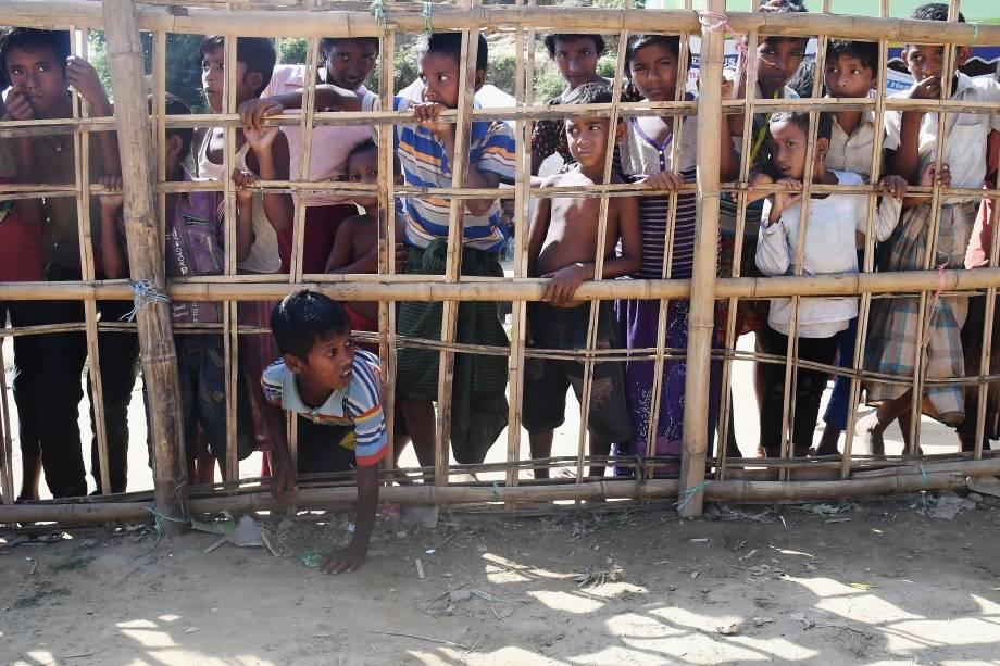 Jovens muçulmanos rohingyas ficam atrás de uma barricada de bambu para coletar comida cozida no campo de refugiados de Thankhali, no distrito de Ukhia, em Bangladesh - 10/11/2017