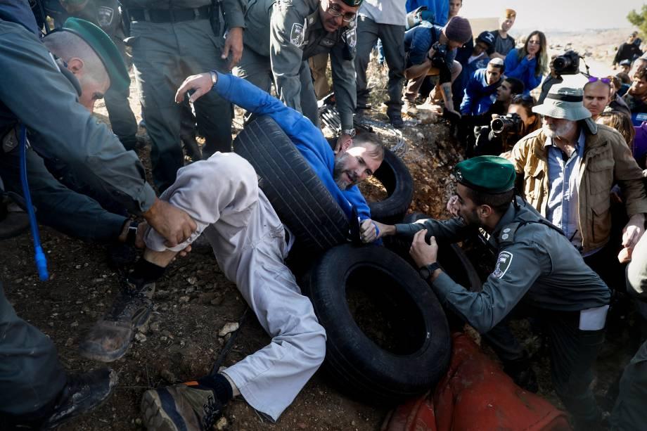 Policiais israelenses evacuam colonos judeus que se escavaram dentro de uma estrutura construída ilegalmente em terras palestinas para evitar sua demolição, no assentamento judeu de Elazar ao sul de Belém, na Cisjordânia - 29/11/2017