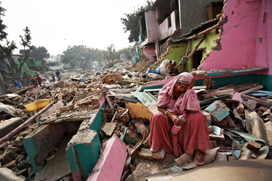 Mulher se senta entre escombros de sua casa, que foi destruída pelas autoridades locais em tentativa de mudar os moradores de local, em Deli, na Índia - 02/11/2017