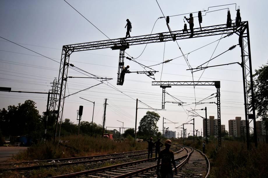 Trabalhadores realizam reparos em linhas de energia, próximo da estação ferroviária de Sabarmati, em Ahmedabad, na Índia - 01/11/2017