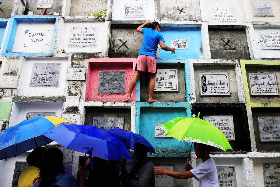 Pessoas visitam túmulos de seus entes queridos no Dia de Todos os Santos, em um cemitério público de Manila, nas Filipinas - 01/11/2017