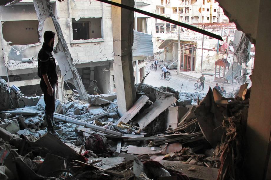 Homem observa apartamento destruído por ataques aéreos, na região de Ghouta, na Síria - 02/11/2017