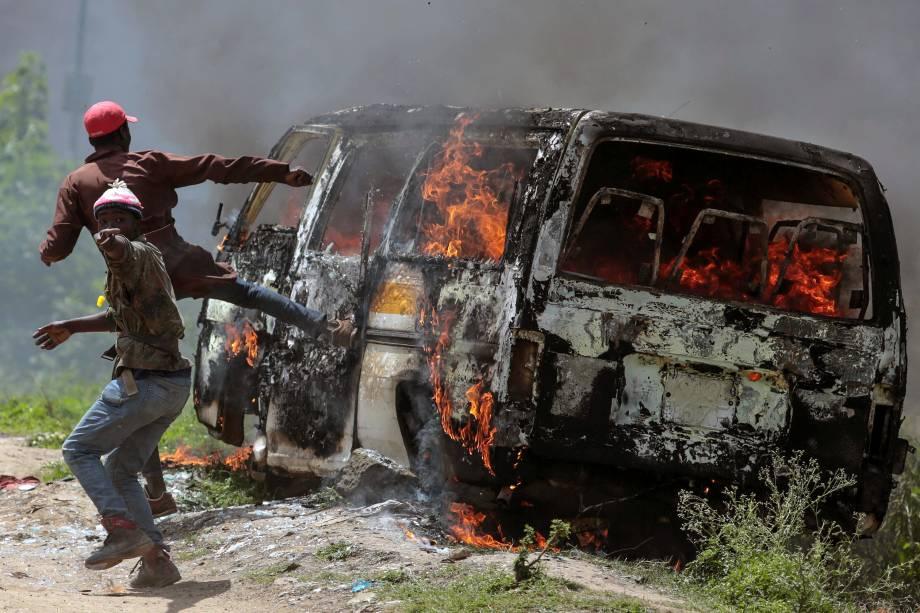 Apoiadores da Super Aliança Nacional (NASA) do Quênia  são fotografados ao lado de um veículo queimado em Embakasi, nos arredores de Nairobi, no Quênia - 28/11/2017