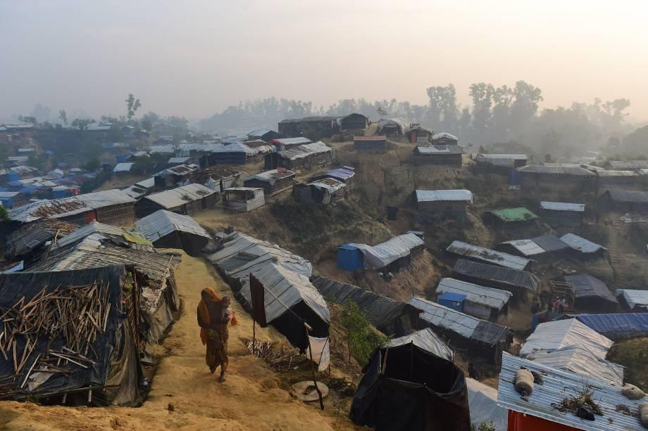 Mulher caminha com uma criança no colo no campo de refugiados de Balukhali, no distrito bengali de Ukhia - 23/11/2017