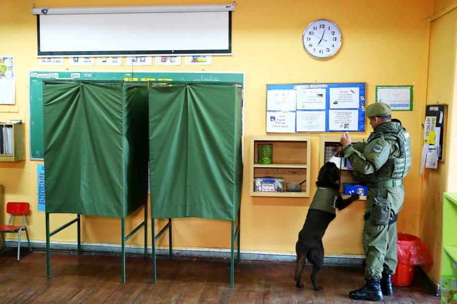 Policial usa cão farejador para inspecionar local de votação, no dia em que ocorre as eleições presidenciais em Santiago, capital do Chile - 19/11/2017