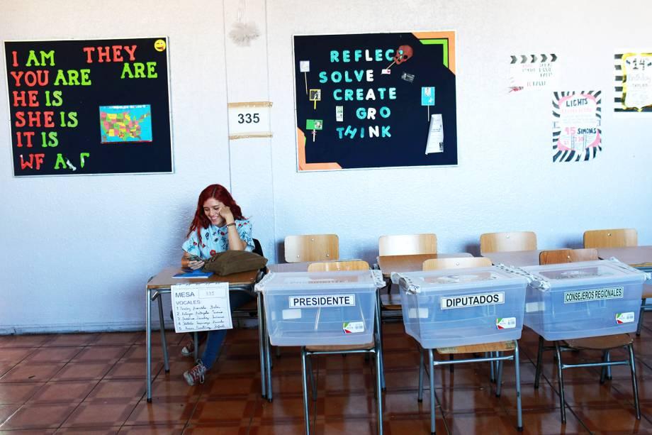 Mesária aguarda eleitores em local de votaçāo em Santiago, capital do Chile - 19/11/2017