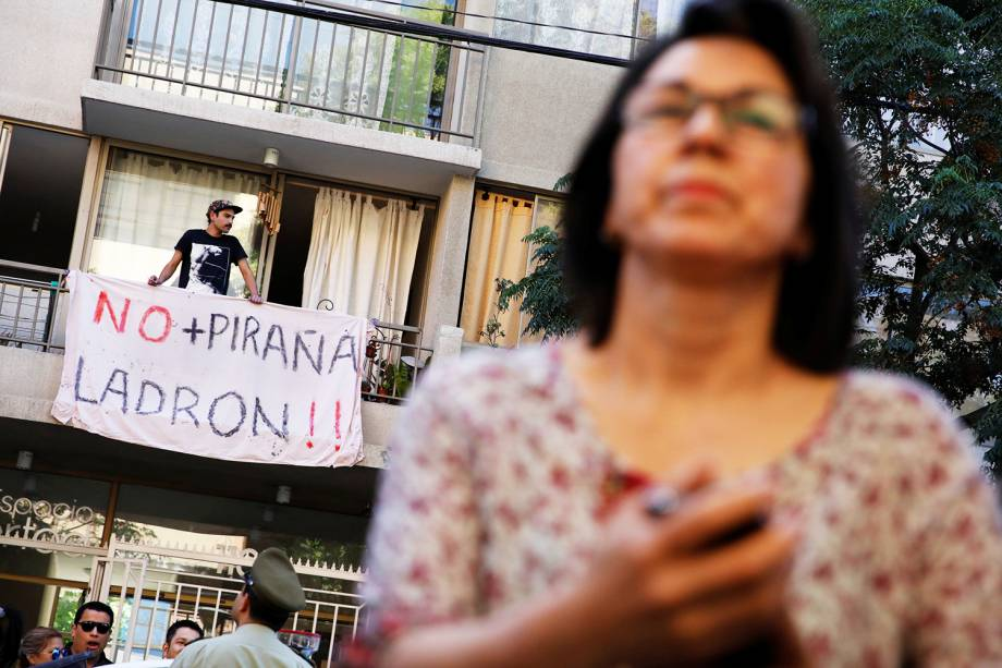 Manifestante com cartaz é visto na frente de escola pública onde o candidato Sebastian Pinera votou durante as eleições presidenciais - 19/11/2017