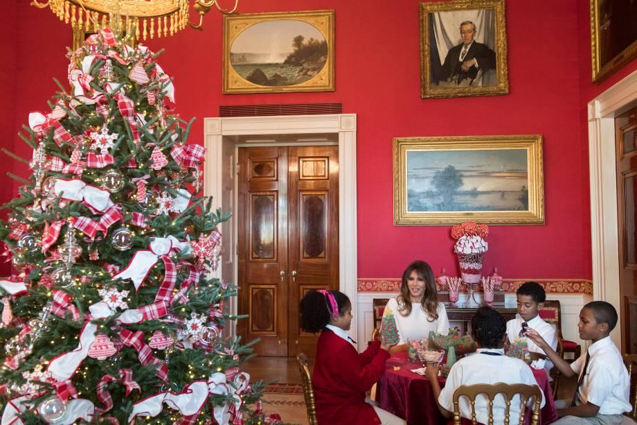 A primeira-dama dos EUA, Melania Trump conversa com um grupo de crianças na Sala Vermelha durante visita às decorações de Natal na Casa Branca, em Washington