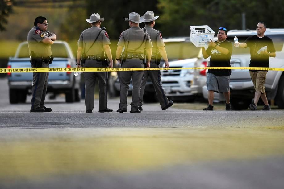 Voluntário distribuem água para policiais, próximos do local onde 26 pessoas morreram após atirador abrir fogo, no estado americano do Texas - 05/11/2017