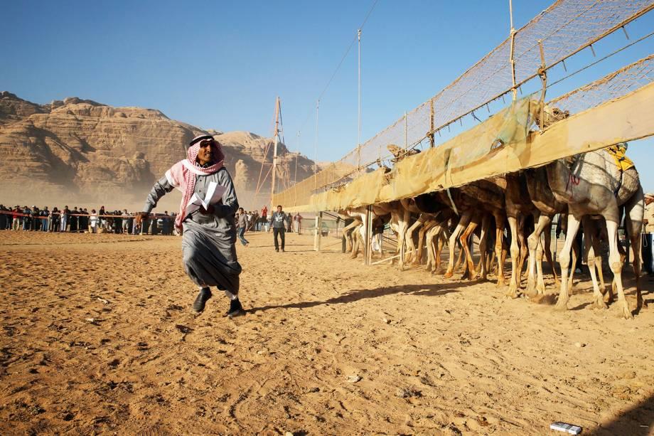 Árbitro dá a largada para camelos correrem, em disputa realizada anualmente no vale de Wadi Rum, na Jordânia - 02/11/2017